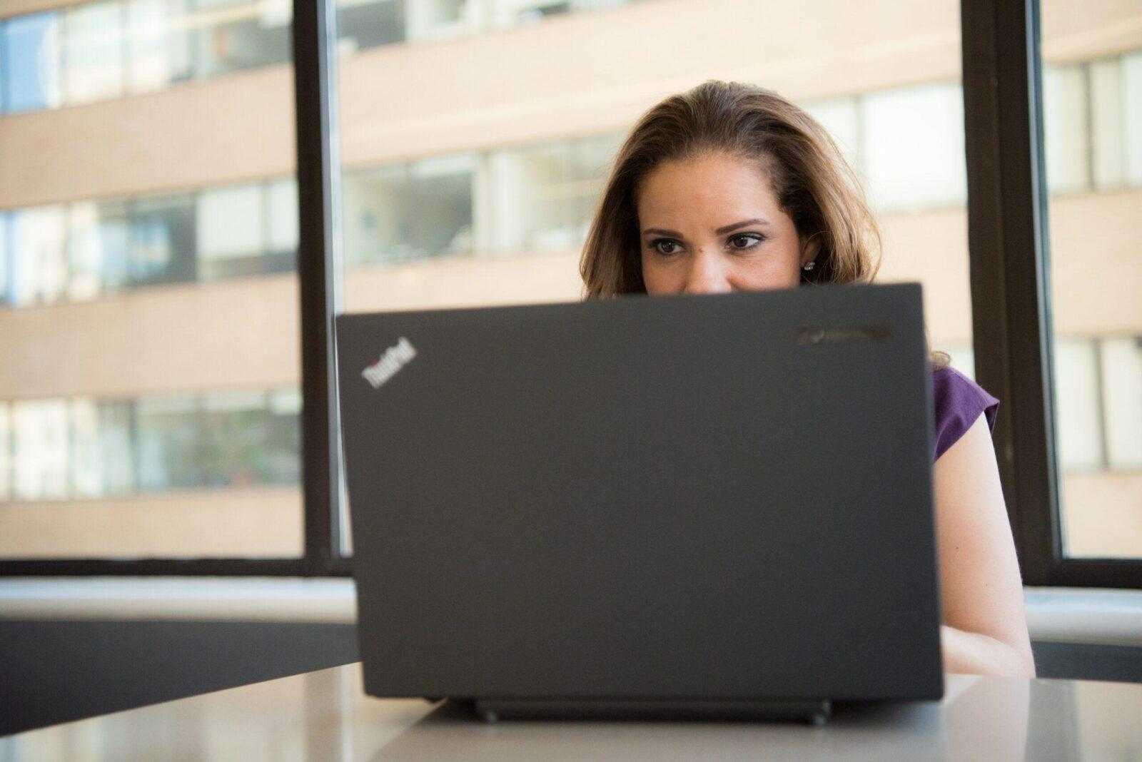 woman using a black Lenovo ThinkPad