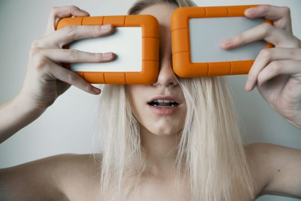 woman holding two white-and-orange plastic cases