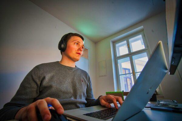 man using MacBook and cordless headphones