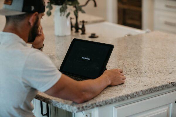 man in white t-shirt using black laptop computer